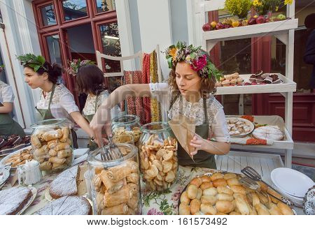 TBILISI, GEORGIA - SEP 25, 2016: Beautiful young girl with flowers in hair selling cookies cakes of a backery during a street festival on September 25, 2016. Tbilisi has population of 1.5 million people