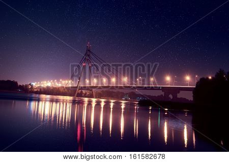 Moscow bridge in Kiev at night with colorful illumination and reflection in Dnieper river