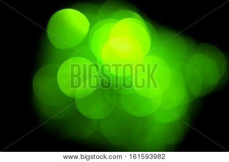 Green blurred lights, bokeh effect. Real photo background. Isolated on black