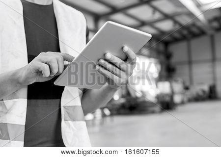 Midsection of manual worker using digital tablet in metal industry