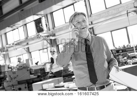 Mature male supervisor with clipboard talking on mobile phone in industry