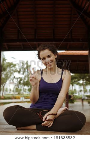 Portrait of smiling young yogini with rosary looking at camera