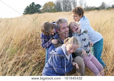 Man with kids playing in field, out in the countryside