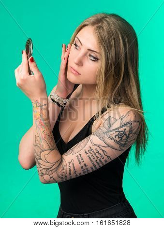Young Woman Checking Her Appearance In A Small Handheld Mirror