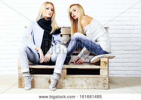Pretty girls or beautiful cute women sexy fashion model with blond hair in jeans and sweatshirt sits on wooden pallet sofa on white brick wall