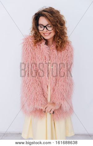 Vertical image of shy smiling woman in glasses and pink fur coat. Isolated gray background
