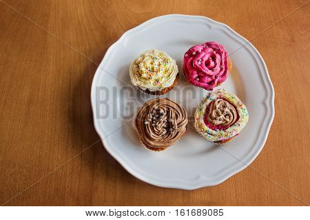 Four different homemade cupcakes in dish over wooden background