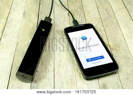 BUNG KAN THAILAND - FEBRUARY 21 2016: Smart phone and facebook messenger app on screen is charging by power bank on wood background
