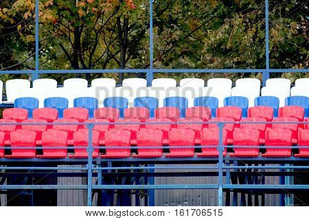 Grandstand stadium with many colored seats outdoors front view