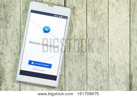BUNG KAN THAILAND - FEBRUARY 19 2016: smart phone display facebook messenger app on wood background space for caption