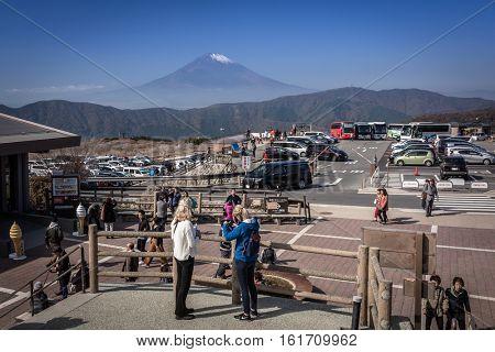 HAKONE, JAPAN - NOVEMBER 7, 2016: Tourists at the volcanic valley of Owakudani with Mount Fuji view, Japan. Owakudani has many active sulphur vents and hot springs in Hakone, Japan.
