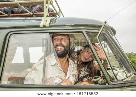 A young couple smile and wave as they head of on a journey in their old classic combi van.