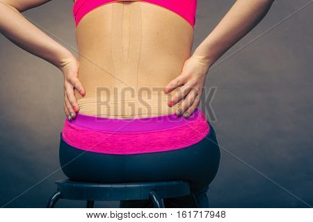 Woman with tape application for back pain. Backache alternative therapy method. Health and body care.