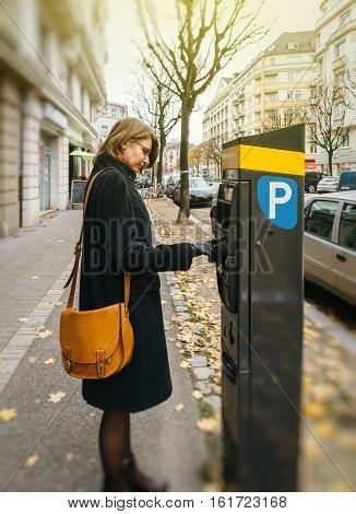 Street scene of woman wearing elegant coat paying for the parking at the teller machine in the city