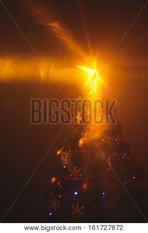 Christmas tree with shining star and dense smoke