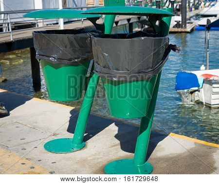 Two green trash cans lined with trash bags mounted on a pier in Cabo San Lucas Mexico