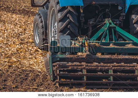 Large tractor pulling a plow and plow the field remove the remnants of the previously beveled sunflower. The work of agricultural machinery. Harvest.