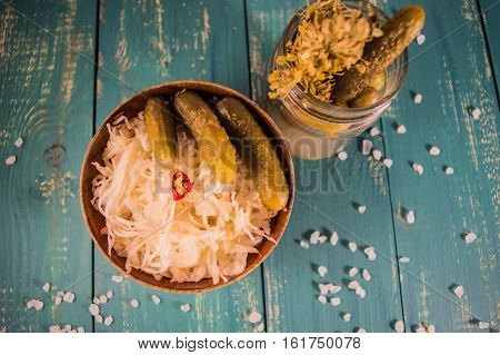 Fresh sauerkraut and pickles. At the turquoise wooden background. Top view.