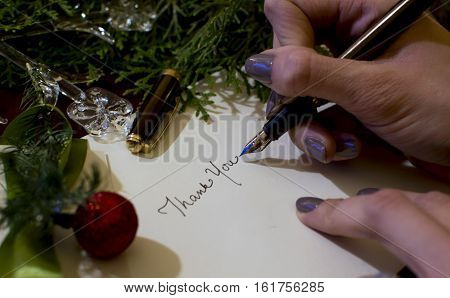 Holiday Thank you card words written by hand on white card stock writing Christmas and new year's seasons greetings gratitude messages to friends family and business partners or social network for personal touch with elegant fountain pen