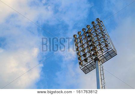 Football stadium spotlight pole on blue sky background