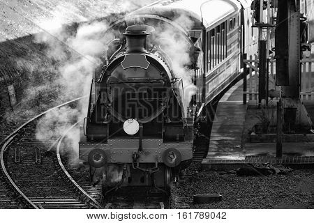 Historic vintage steam railway engine in station with full steam puffing in black and white