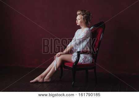 shy and Young beautiful bride in elegant white robe sitting on a chair in a marsala interior.