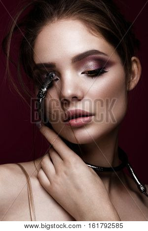 Beautiful girl with bright makeup and a fashionable hairdo with decoration in the form of a snake. The beauty of the face. Portrait shot in studio
