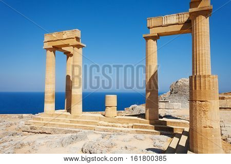 Lindos ancient Acropolis ruins with columns and portico against the beautiful view of Aegean sea