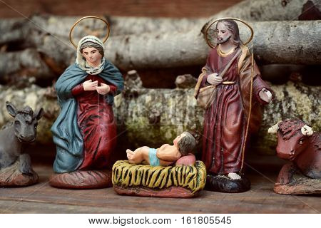 the holy family, the Child Jesus, the Virgin Mary and Saint Joseph, and the donkey and the ox in a rustic nativity scene