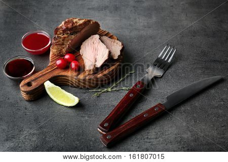 Composition of tasty steak, knife, fork and ingredients on kitchen table