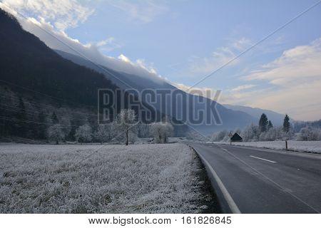 A road near Tolmin in Primorska Slovenia cutting through a landscape covered in hoar frost