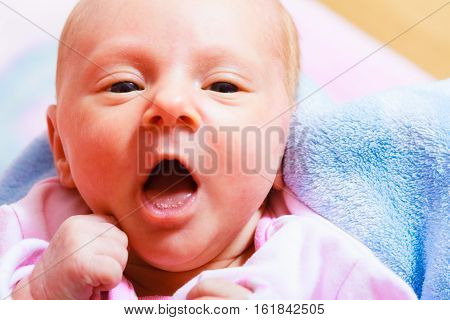 Little newborn baby in pyjamas lying on back. Face expression. Family parenthood childhood concept.