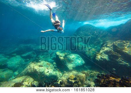 Young woman snorkeling in the blue waters of the popular Similan Islands in Thailand, one of the tourist attraction of the Andaman Sea.