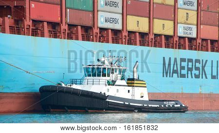 Oakland CA - December 13 2016: Tugboat DELTA CATHRYN assisting cargo ship GERD MAERSK maneuver into the Port of Oakland the fifth busiest port in the United States.