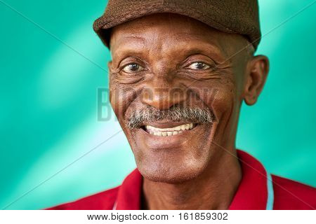 Real Cuban people and feelings portrait of happy senior african american man looking at camera. Cheerful old latino grandfather with mustache and hat from Havana Cuba