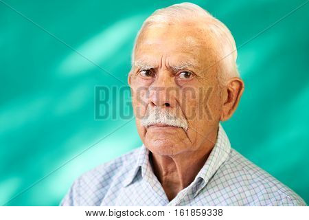 Real Cuban people and feelings portrait of sad senior hispanic man looking at camera. Worried old latino grandfather with mustache from Havana Cuba