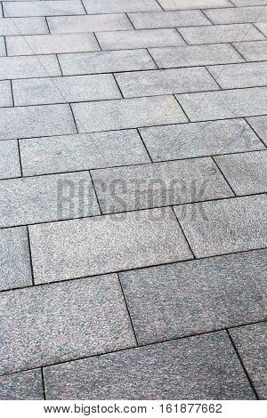 large granite slabs on the sidewalk, vertical image