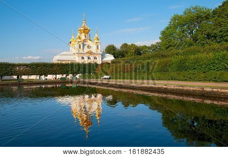 PETERHOF, SAINT - PETERSBURG, RUSSIA - AUGUST 19, 2016: The Upper Garden. The Eastern Square Pond and The Grand Palace Church of Saints Peter and Paul