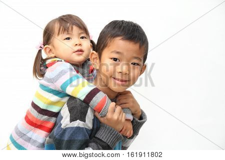 Japanese boy carrying his sister on his back (7 years old boy and 2 years old girl)