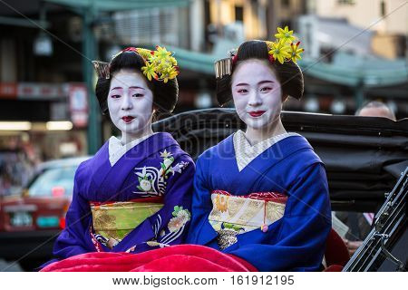KYOTO, JAPAN - NOVEMBER 11, 2016: Maiko women, apprentice geisha on the street of Kyoto, Japan. Their jobs consist of performing songs, dances, and playing the shamisen
