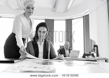 Businesswomen reading book with male colleague in background at office