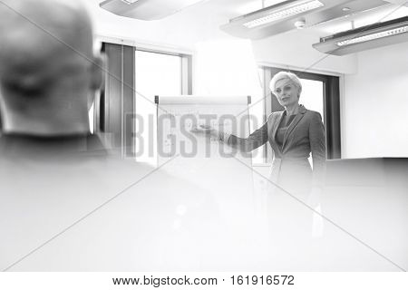 Mature businesswoman giving presentation to male colleague in board room