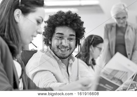 Young businessman discussing with businesswoman with colleagues in background at office