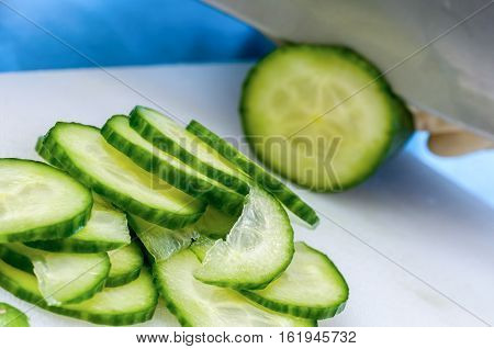 Knife in the process of manually slicing a length of cucumber on a chopping board. Some freshly sliced portions are in the foreground of the image.