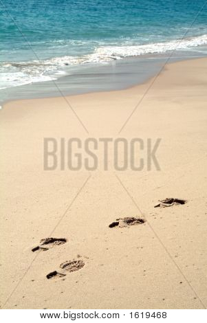 Footprints On Sand In The Beach