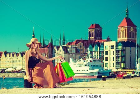 Spending money buying things concept. Fashionable woman resting after big shopping sitting with bags wearing glamorous outfit and big sun hat Gdansk old town in background