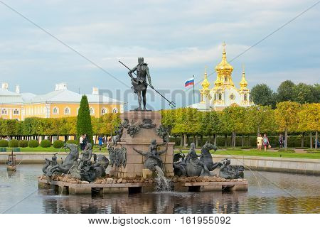 PETERHOF, SAINT - PETERSBURG, RUSSIA - AUGUST 19, 2016: The Upper Garden. The Neptune Fountain. On the background is The Grand Palace and The Church of Saints Peter and Paul