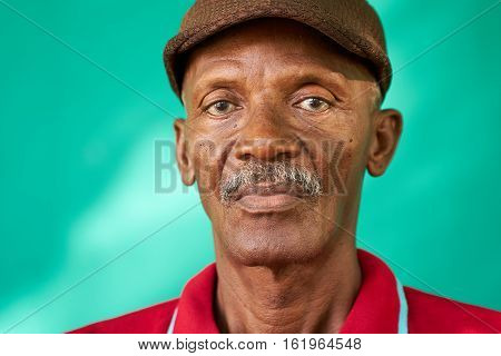Real Cuban people and feelings portrait of sad senior african american man looking at camera. Worried old latino grandfather with mustache and hat from Havana Cuba