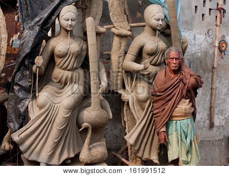 KOLKATA, INDIA - JAN 15, 2013: Older man and artictic sculptures at historical Kumartuli artistic area on January 15, 2013 in India. Populat. of Kolkata is 4.5 million out 25 million are males