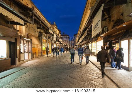 Tourists Near Shops On Ponte Vecchio In Evening